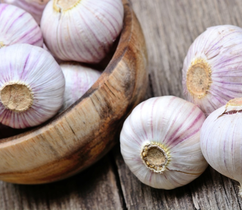 Fresh garlic in a bowl on rustic table
